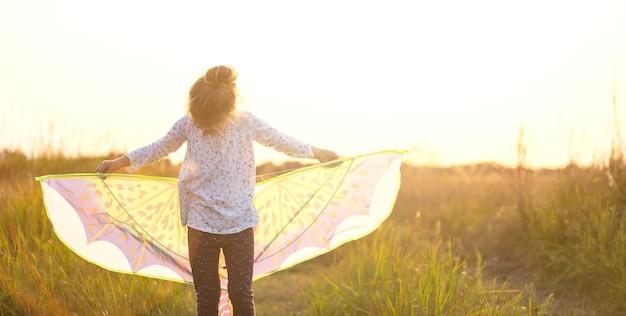 Meisje staat met vleugels in het veld en leert vliegeren. outdoor entertainment in de zomer, natuur en frisse lucht. jeugd, vrijheid en zorgeloosheid. de dromen en hoop van kinderen