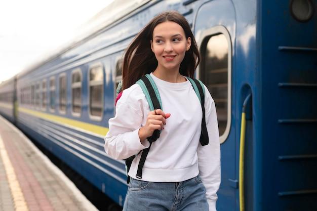 Meisje staat naast de trein met haar rugzak