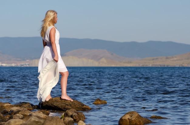 Meisje staat op een rots en kijkt naar zee