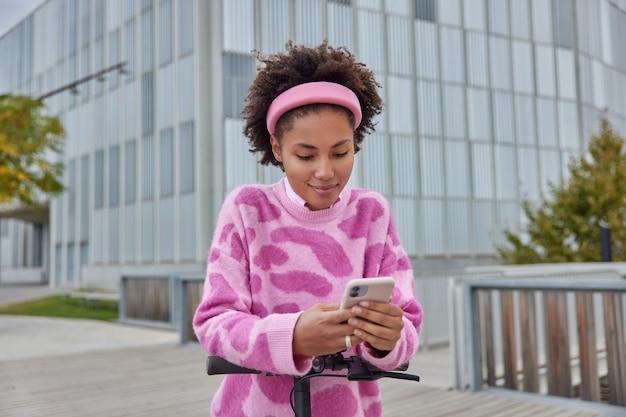 Meisje staat op elektrische step gebruikt smartphone poses in moderne stad draagt roze hoofdband en jumper modern glazen business center gebouw op de achtergrond