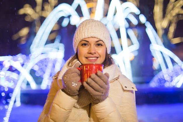Meisje staat over winterkerststad achtergrond sneeuw sneeuw drifts, staat warme jas hoed, houdt kopje thee met warme theedranken.