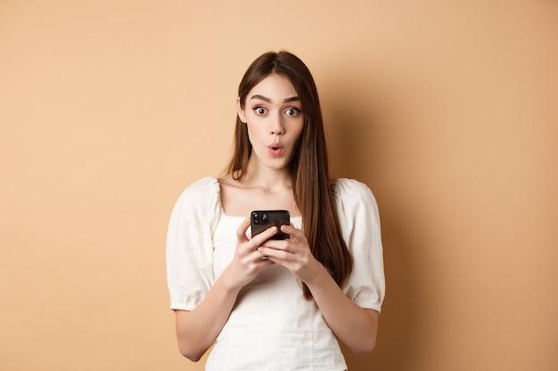 Meisje staat verbaasd met smartphone, zegt wow en kijkt opgewonden door geweldig nieuws over online aanbiedingen, staande op een beige achtergrond.