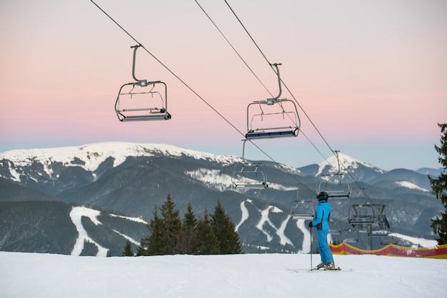 Meisje staat zijwaarts op ski's en houdt stokken in de hand op een achtergrond van skiresort en afdaling van de sneeuwberg