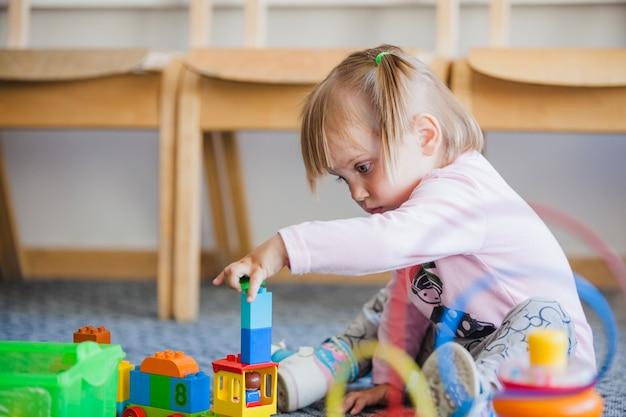 Meisje stapelen speelgoed in speelkamer