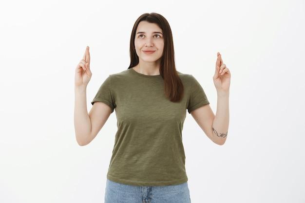 Meisje steekt gekruiste vingers omhoog in de lucht en ziet er dromerig en hoopvol uit met een optimistische glimlach die wens doet, in de hoop dat de droom uitkomt, bidt voor fortuin en geluk over grijze muur, anticiperend