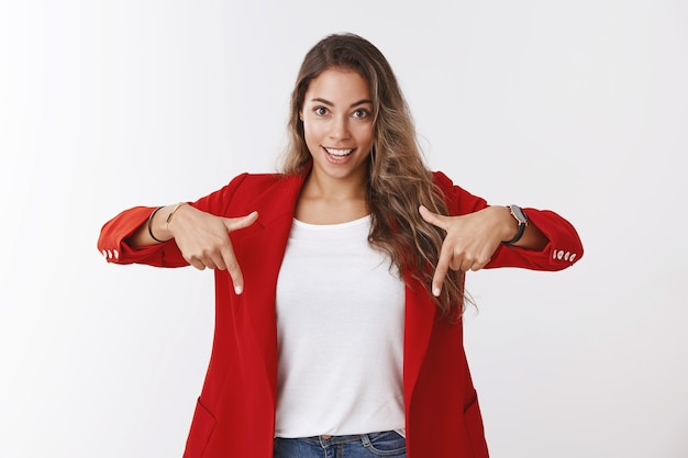 Meisje stelt voor om naar beneden te kijken, geweldige promotie verhoogt het bedrijfsinkomen. opgewonden, knappe assertieve jonge vrouwelijke ondernemer die een rood jasje draagt dat naar beneden wijst met een glimlachende ambitieuze, witte muur