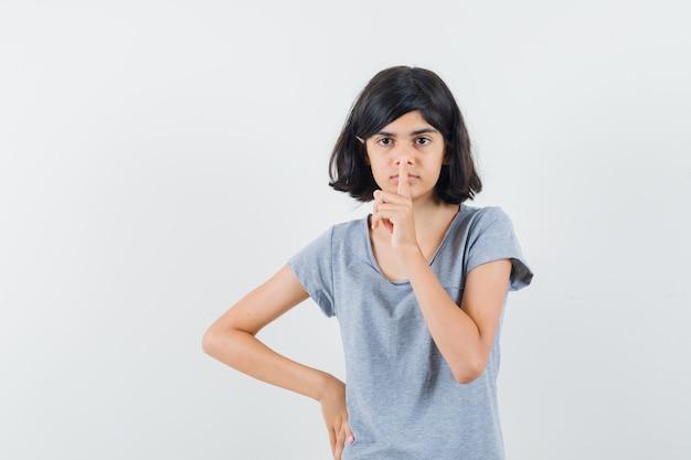 Meisje stilte gebaar in t-shirt tonen en peinzend kijken. vooraanzicht.