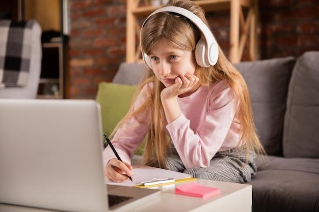Meisje studeert door groepsvideogesprek, gebruik videoconferentie met leraar, luisterend naar online cursus.