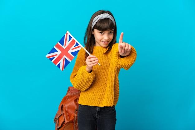 Meisje studeert engels geïsoleerd op een blauwe achtergrond die een vinger laat zien en optilt