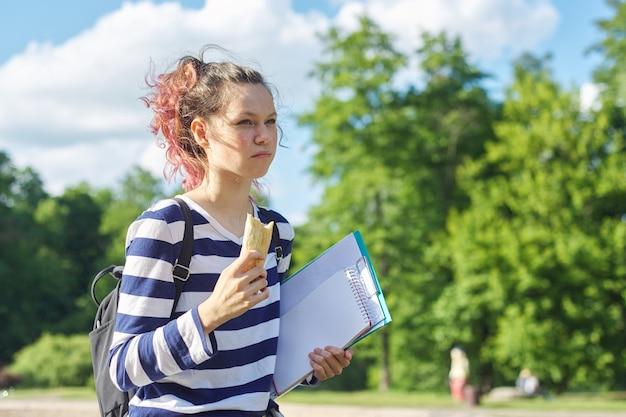 Meisje student buiten lopen met rugzak