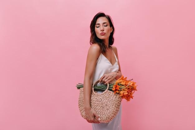 Meisje stuurt kus en houdt tas met bloemen op roze achtergrond