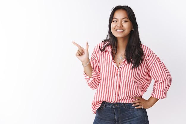 Meisje suggereert vriend wat kopen voor valentijnsdag maakt indruk op vriendin, pont in de linkerbovenhoek met een tevreden vrolijke glimlach als het juiste cadeau voor haar kiezen, trots en verrukt poseren over witte muur