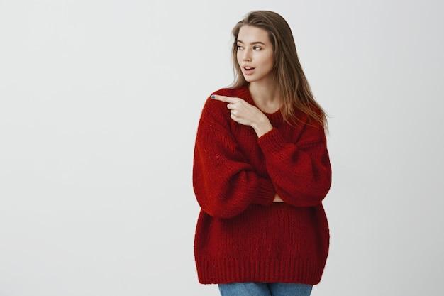 Meisje suggereert vrienden om de bar in die richting te raken. gerichte ernstige aantrekkelijke vrouw in losse rode trui, kijken en wijzen naar links, interessante cafe bespreken, staande over grijze muur