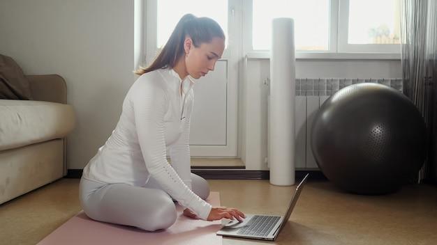 Meisje surft op internet met laptop om oefeningen op kamer te vinden