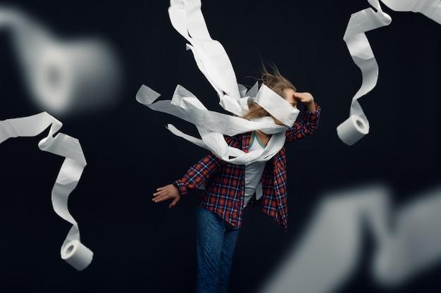 Meisje tegen krachtige luchtstroom, haar, winderig effect ontwikkelen, rollen wc-papier vliegen in de studio. kinderen en wind, kind geïsoleerd op een donkere achtergrond, kind emotie