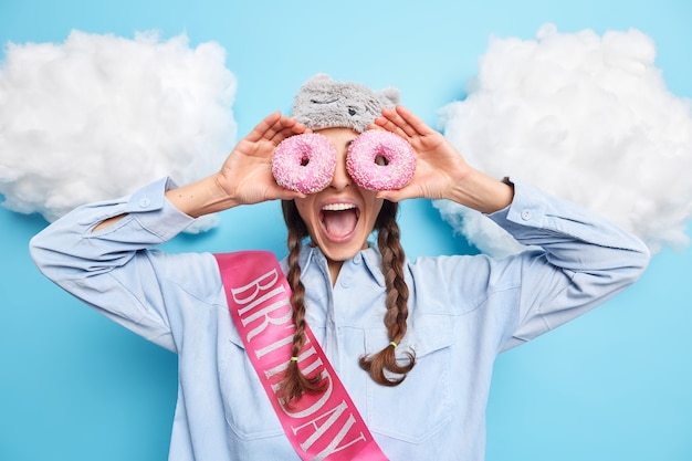 Meisje tegen ogen met geglazuurde donuts houdt mond open gekleed in shirt met lint heeft plezier op verjaardag geïsoleerd op blauw