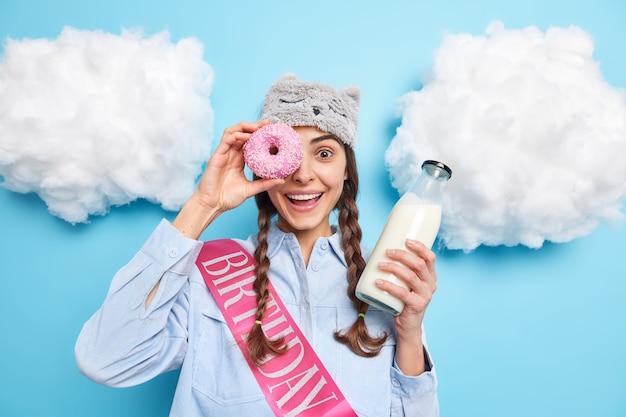 Meisje tegen oog met heerlijke geglazuurde donut op oog glimlacht aangenaam houdt glazen fles melk viert verjaardag alleen geïsoleerd op blauw