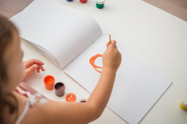 Meisje tekent een close-up in het album met een penseel in oranje kleuren