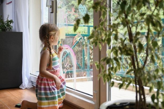 Meisje tekent een regenboog op het raam selectieve focus