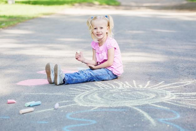 Meisje tekent met krijt op stoep