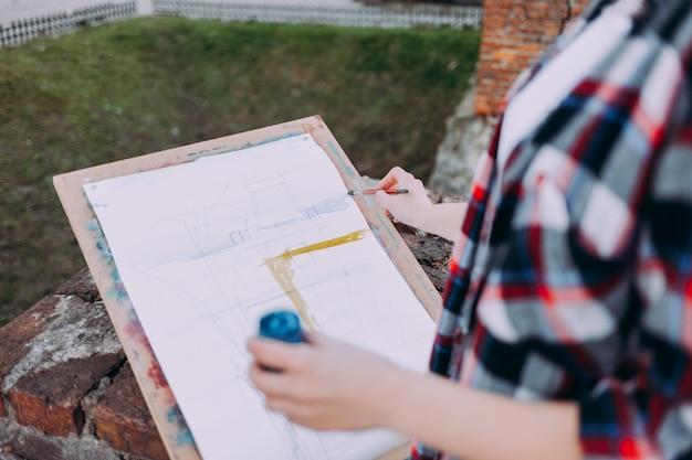 Meisje tekent op een bord voor kunstenaars direct aan de stadsstraat.