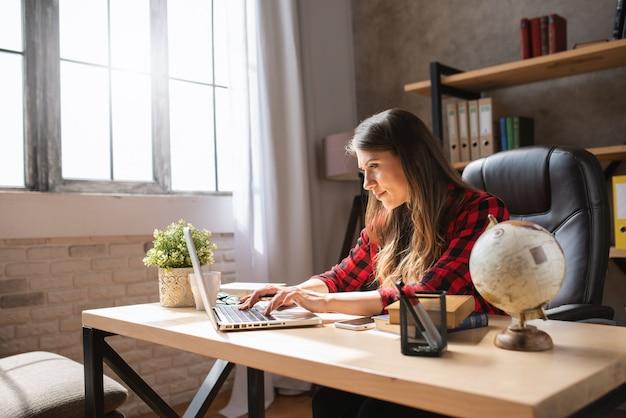 Meisje telewerker werkt thuis met een laptop