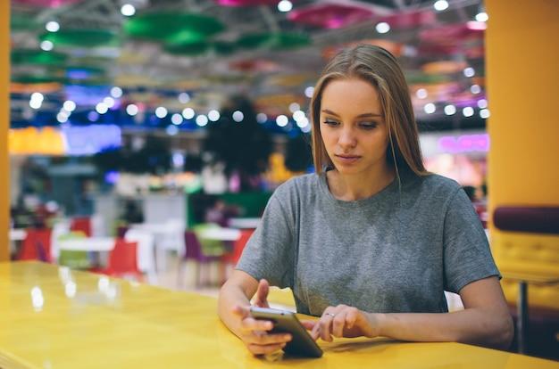 Meisje texting op de slimme telefoon op het terras van een restaurant