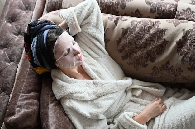 Meisje thuis hydrateert de huid van het gezicht