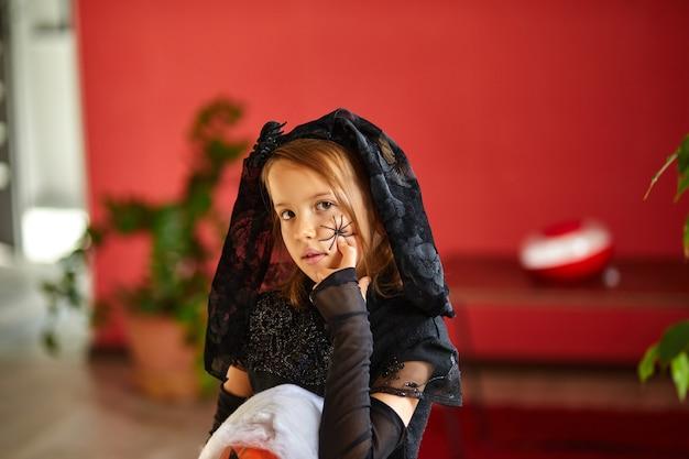 Meisje thuis in halloween kostuum met pompoen jack of laurent in handen, kind met zwart gezichtsmasker bescherming tegen coronavirus, halloween in quarantaine