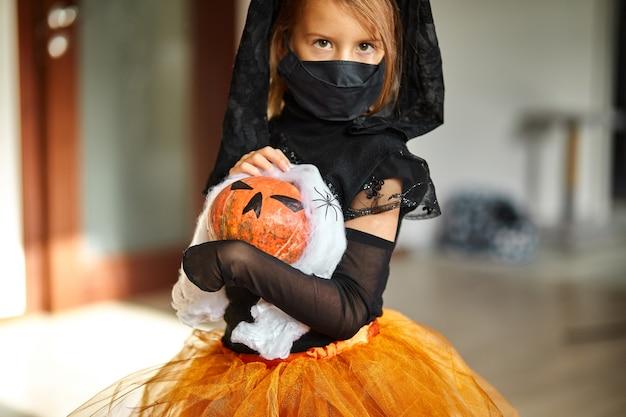 Meisje thuis in halloween-kostuum met pompoen jack of laurent in handen, kind met zwart gezichtsmasker dat beschermt tegen coronavirus, halloween in quarantaine.