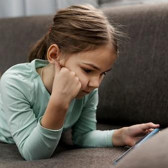Meisje thuis spelen op een smartphone