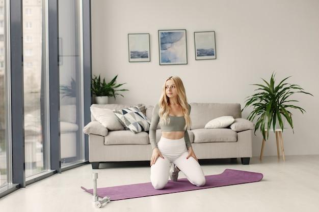 Meisje thuis. vrouw maakt yoga. dame met halters.