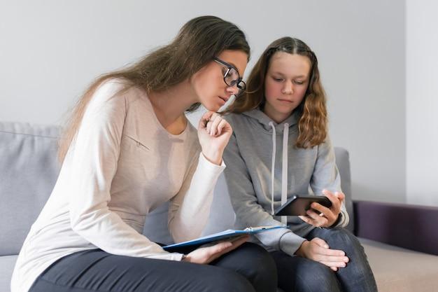 Meisje tiener 14, 15 jaar oud praten met vrouw psycholoog