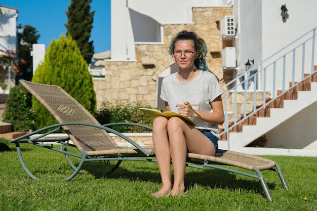 Meisje tiener 15, 16 jaar oud zittend op een ligstoel op het gazon, schrijven met potlood in notitieblok. terug naar school, zomer start van de lessen