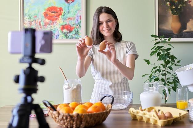 Meisje tiener food blogger koken oranje pannenkoeken thuis in de keuken. ingrediënten producten meel, sinaasappels, melk, suiker, eieren op tafel. kookhobby's volgerskanaal voor meisjes, tieners en kinderen