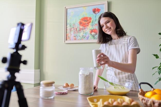 Meisje tiener food blogger koken oranje pannenkoeken thuis in de keuken. vrouw giet suikermeel, moderne jeugd, hobby en vrije tijd, gezond lekker zelfgemaakt voedselconcept