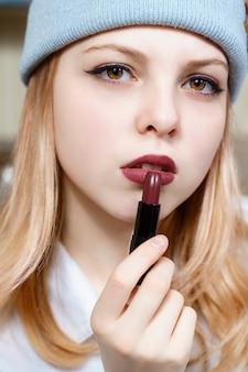 Meisje tiener in een blauwe hoed houdt felle lippenstift in haar hand.
