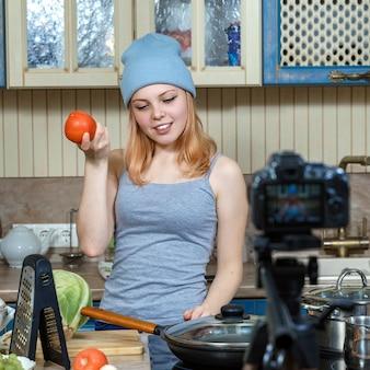 Meisje tiener jonge voedsel blogger bereidt voedsel, schrijft het recept naar de camera.