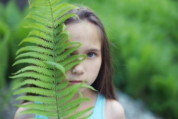 Meisje tiener met lang haar kijkt naar de camera halverwege achter een blad van varens.