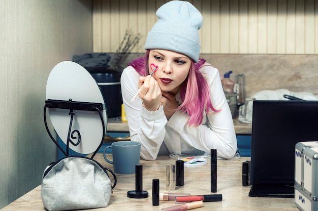 Meisje tiener met roze haren maakt lichte make-up thuis voor de spiegel.