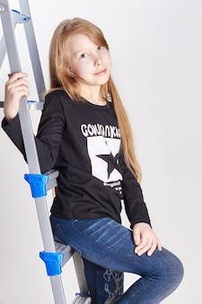Meisje tiener zittend op de ladders. jong model poseren op lichte achtergrond. natuurlijke schoonheid, jong kind