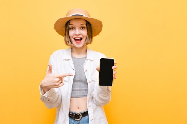 Meisje toerist in hoed en zomer kleding toont smartphone met zwart scherm en vinger op scherm, kijkt naar camera met blij gezicht