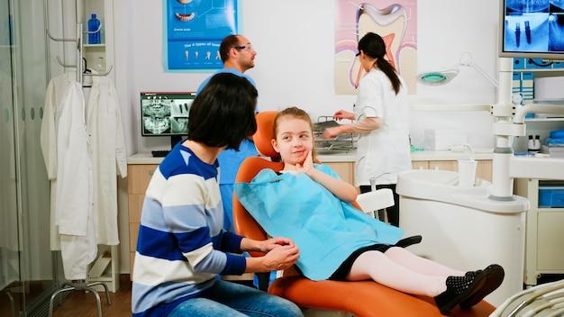 Meisje toont aan moeder getroffen massa zittend op stomatologische stoel praten met haar moeder terwijl team van stomatoloog artsen tanden röntgenfoto analyseren van kleine patiënt met kiespijn op achtergrond