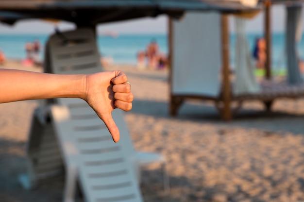 Meisje toont haar afkeer naar zee, strand met haar duim naar beneden