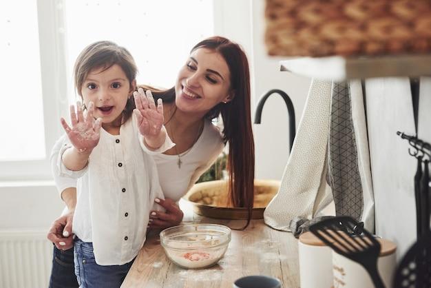 Meisje toont haar handen vol meel. gelukkige dochter en moeder bereiden samen bakkerijproducten. kleine helper in de keuken.