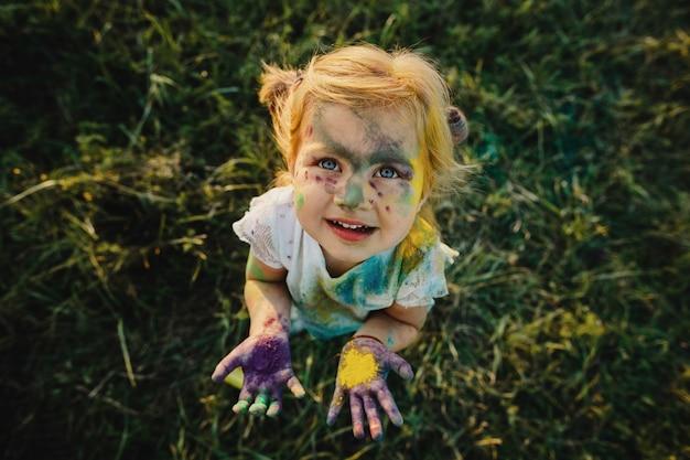Meisje toont haar kleine handpalmen bedekt met kleurrijke verf