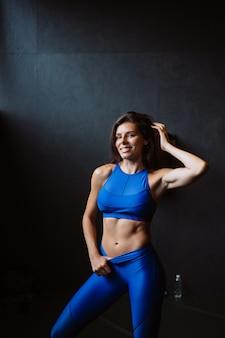 Meisje toont haar opgepompte buikpers. atletisch lichaam na dieet en zware inspanning, slanke taille