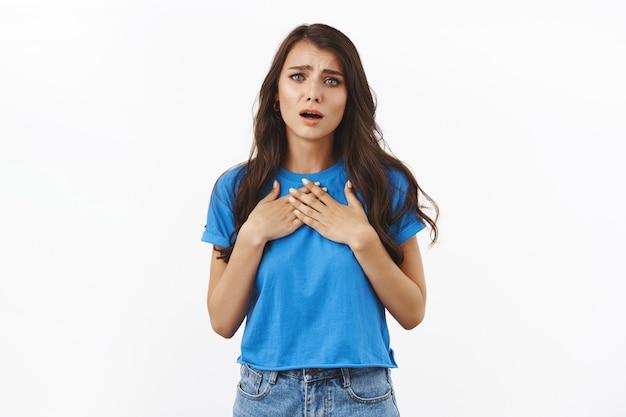 Meisje toont medeleven en sympathiseert hartverwarmend verhaal, drukt de handen op de borst, zuchtend en fronsend aangeraakt, gevoelens bewogen door romantische lieve woorden, witte muur