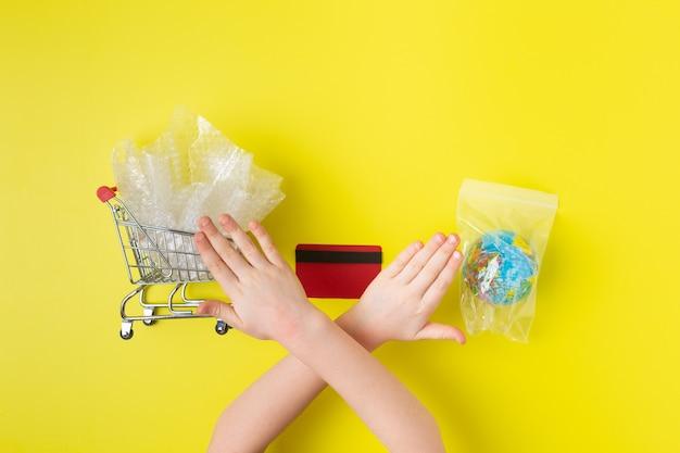 Meisje toont met handen om plastic vervuiling te stoppen.