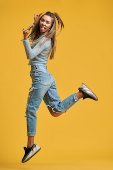 Meisje toont tong v teken in sprong